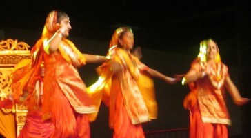 A swirl of Bhangra dancers on stage