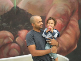 "Artist Elio Mercado aka EVOCA1 with son, mural ""Hometown Choice"" in the background."