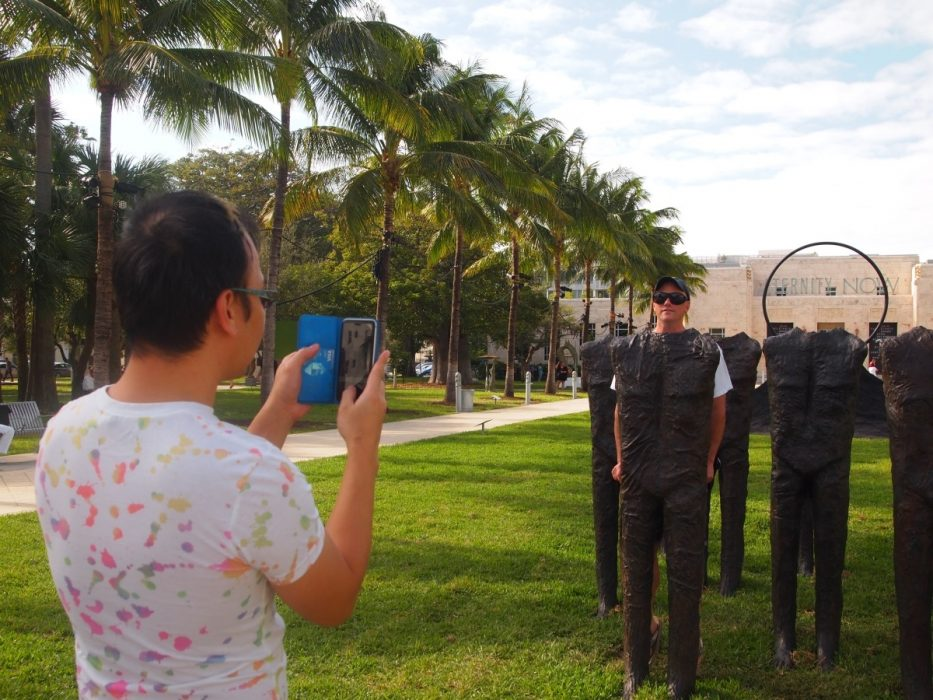 "Photo Time!: Taking picture by ""100 Standing Figures"" by Magdalena Abakanowicz, displayed at Art Basel Public showcase in Collins Park, Miami Beach"