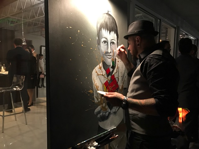 Kevin Vigil, of Miami, works on a painting during a VIP reception for Art Fort Lauderdale.
